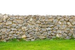Fäkta verklig yttersida för stenväggen med cement på fält för grönt gräs Royaltyfri Bild