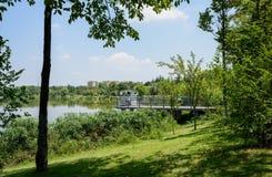 Fäktad plattform på den grönskande lakesiden i solig sommareftermiddag royaltyfri bild