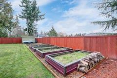 Fäktad trädgård med grönt gräs och lyftta sängar royaltyfria foton