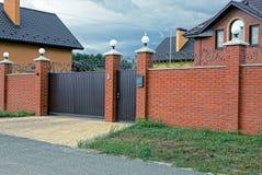 Fäktar den brunt järn stängda portar och delen av en lång tegelsten i gatan royaltyfri foto