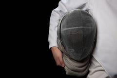 Fäktarekvinnan rymmer hennes hjälm i bärande vit fäktningdräkt för hand Isolerat på svart bakgrund royaltyfria foton