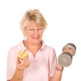 Fällige ältere Dame, die Diät oder Übung wählt Stockbilder