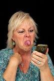 Fällige blonde Frau mit Handy (9) Stockfotografie