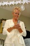 Fällige Dame auf einer Party, die SMS sendet Stockfoto