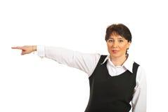 Fällige Frau des Geschäfts, die auf die Seite zeigt stockbilder