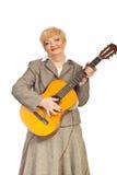 Fällige Frau, die Akustikgitarre spielt Lizenzfreies Stockfoto