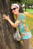 Fällige Frau, die auf Baum sich lehnt Stockfotografie