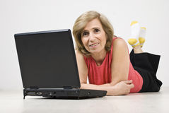 Fällige Frau, die auf Fußboden unter Verwendung des Laptops liegt Lizenzfreie Stockfotos