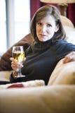 Fällige Frau, die auf trinkendem Wein des Sofas sich entspannt Lizenzfreies Stockbild