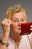 Fällige Frau, die Augenschminke anwendet lizenzfreies stockfoto