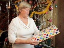 Fällige Frau, die ein Geschenk des neuen Jahres anhält Lizenzfreie Stockfotografie