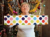 Fällige Frau, die ein Geschenk des neuen Jahres anhält. Stockbilder