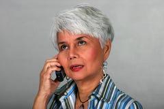 Fällige Frau, die einen Handy verwendet lizenzfreie stockbilder