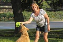 Fällige Frau, die mit ihrem Hund spielt. Stockfotos