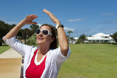 Fällige Frau, die am sonnigen Tag sich entspannt stockfotografie