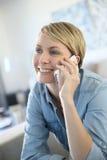 Fällige Frau, die am Telefon spricht Stockbilder