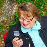 Fällige Frau, die Telefon verwendet stockbilder