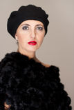 Fällige Frau im Pelz auf grauem Hintergrund stockbild