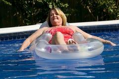 Fällige Frau am Swimmingpool. Lizenzfreies Stockbild