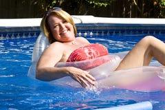 Fällige Frau am Swimmingpool. Stockbilder