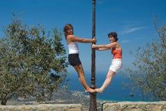 Fällige Frau und junges Mädchen, die auf einer Laterne steht Stockfotografie