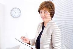 Fällige Geschäftsfrau im Büro lizenzfreie stockfotos