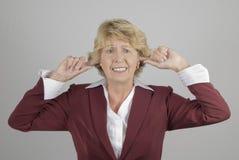 Fällige Geschäftsfrau mit den Fingern in den Ohren Lizenzfreie Stockfotografie
