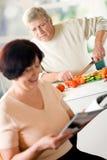 Fällige glückliche Paare, die an der Küche kochen stockfotos
