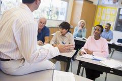 Fällige Kursteilnehmer und ihr Lehrer in einem Klassenzimmer Lizenzfreie Stockbilder