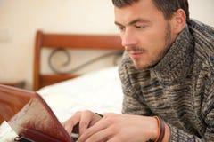 Fällige Männer, die online in seinem Haus arbeiten Stockfoto