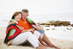 Fällige Paare, die auf dem Strand sitzen. Lizenzfreie Stockfotografie
