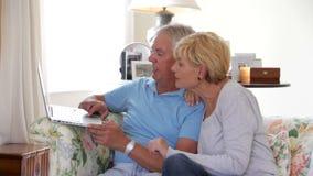 Fällige Paare, die auf Sofa unter Verwendung des Laptops sitzen stock video footage