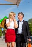 Fällige Paare, die durch das Stadteinkaufen schlendern Stockfoto