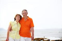 Fällige Paare, die entlang den Strand gehen. stockfotografie