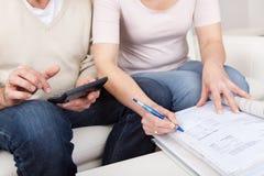 Fällige Paare, die Familienfinanzen tun Stockbilder