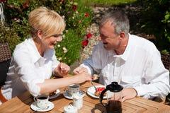 Fällige Paare, die Kaffee auf Portal trinken Stockfotos