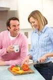 Fällige Paare, die Mahlzeit in der inländischen Küche vorbereiten Lizenzfreies Stockfoto