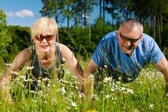 Fällige Paare, die Sport - Pushups tun lizenzfreie stockfotografie
