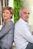 Fällige Paare, die zurück zu Rückseite sitzen Stockfotos