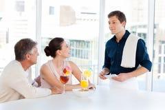 Fällige Paare mit einem Kellner Stockfotografie