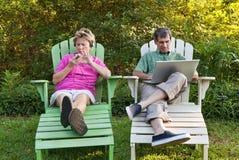 Fällige Paare mit ihren elektronischen Geräten Lizenzfreie Stockfotografie
