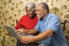 Fällige Paare unter Verwendung des Laptops Stockbilder