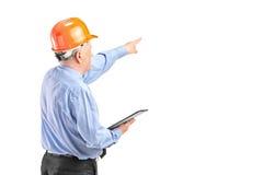 Fälliger Bauarbeiter, der ein Klemmbrett anhält Stockbild