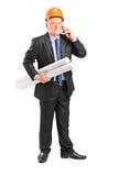 Fälliger Bauarbeiter, der an einem Telefon spricht Lizenzfreie Stockfotos