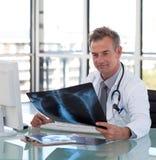 Fälliger Doktor, der einen Röntgenstrahl betrachtet Stockfotos