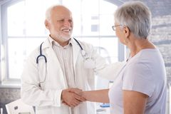 Fälliger Doktor und älterer Patient, die Hände rüttelt lizenzfreie stockfotos