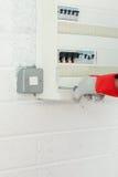 Fälliger Elektriker, der einen Leistungplan bei der Arbeit repariert Stockfoto