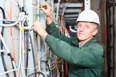 Fälliger Elektriker, der im harten Hut mit Seilzügen arbeitet Stockfoto
