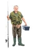 Fälliger Fischer, der eine Fischereiausrüstung anhält Lizenzfreie Stockfotos
