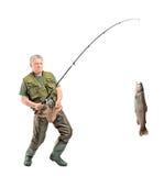 Fälliger Fischer, der einen Fisch abfängt Lizenzfreie Stockfotos